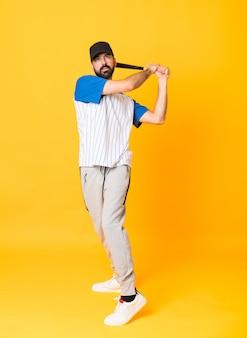 Prise de vue complète de l'homme au jaune isolé jouant au baseball