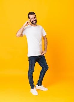 Prise de vue complète de l'homme à la barbe sur fond jaune isolé avec des lunettes et souriant