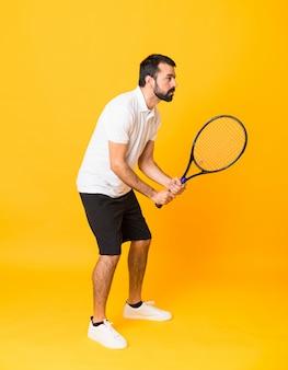 Prise de vue complète de l'homme sur fond jaune isolé, jouer au tennis