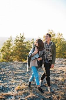 Prise de vue complète jeune couple marchant dans le parc