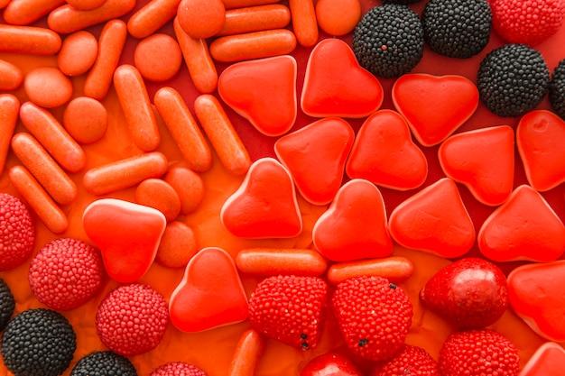 Prise de vue complète de petits fruits, de bonbons en forme de cœur et de bonbons en capsule