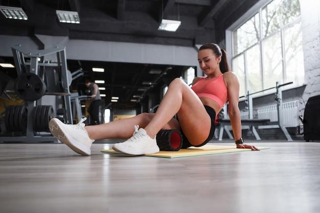 Prise de vue en contre-plongée d'une athlète féminine se relaxant après l'entraînement des jambes, à l'aide d'un rouleau en mousse sur les ischio-jambiers