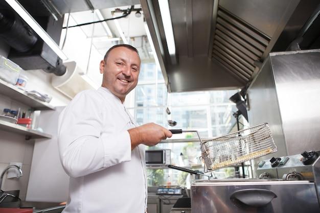 Prise de vue en contre-plongée d'un chef masculin joyeux souriant à la caméra, tout en préparant des frites