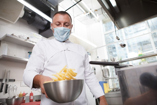 Prise de vue en contre-plongée d'un chef portant un masque médical, faisant des frites au restaurant