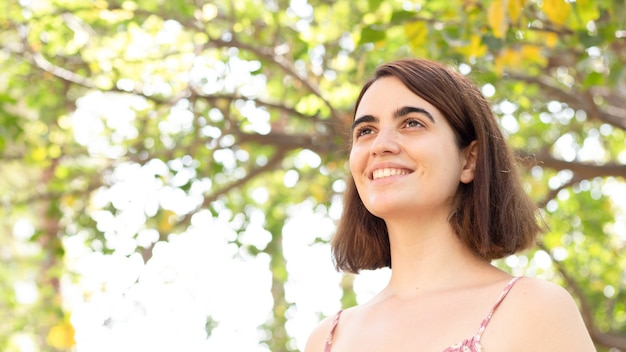 Prise de vue en contre-plongée d'une jeune femme posant dans un parc