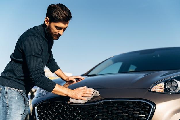 Prise de vue en contre-plongée d'un jeune homme heureux en train de polir sa voiture avec un chiffon en microfibre tout en se sentant satisfait pendant la journée d'été ensoleillée. stock photo