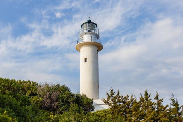 Prise de vue en contre-plongée d'un phare avec un ciel bleu nuageux vu à travers les arbres