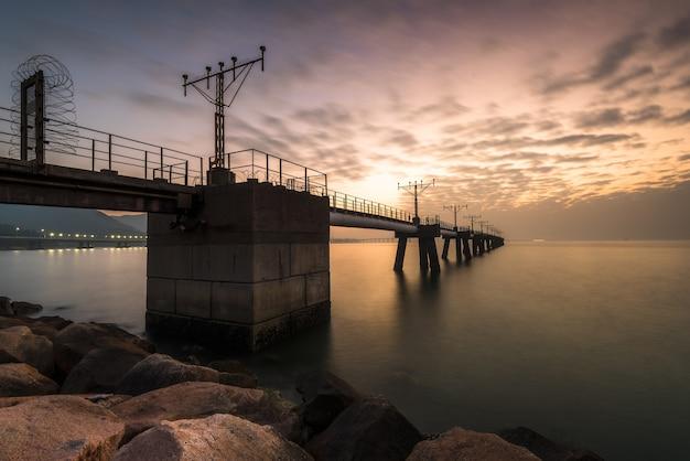 Prise de vue en contre-plongée d'un pont suspendu au-dessus du magnifique océan capturé au coucher du soleil