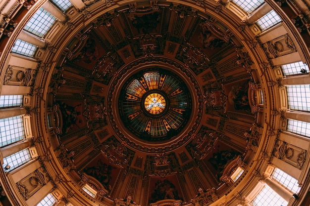 Prise de vue à faible angle de la belle peinture et fenêtres sur un plafond dans un immeuble ancien