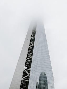 Prise de vue à faible angle d'un gratte-ciel moderne recouvert de brouillard