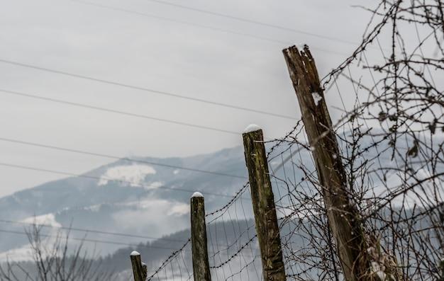 Prise de vue à faible angle d'une vieille clôture avec des colonnes en bois patiné et des fils barbelés