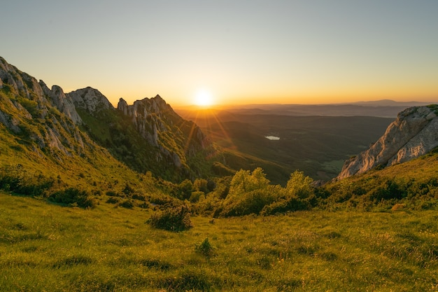 Prise de vue fascinante d'une colline rocheuse verte pendant la belle heure du coucher du soleil