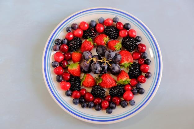 Prise de vue en grand angle d'une assiette de raisins, fraises, cerises, mûres et myrtilles