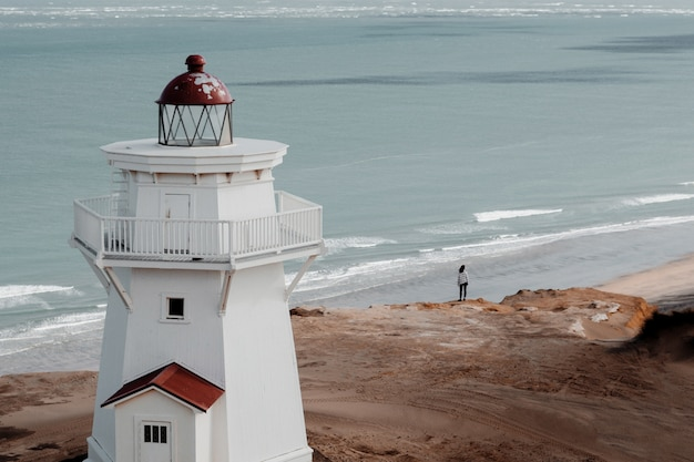 Prise de vue en grand angle d'un beau phare sur la plage avec vue sur l'océan