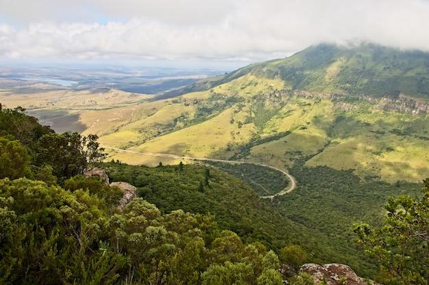 Prise de vue en grand angle de la belle montagne couverte d'arbres et vallées sous le ciel nuageux