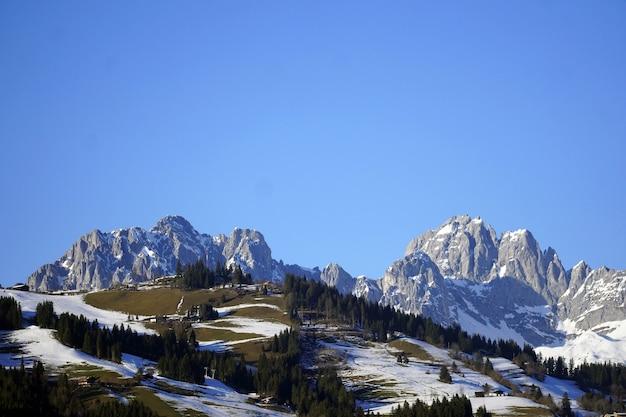 Prise de vue en grand angle d'une belle vallée enneigée et les rochers sous le ciel dans le