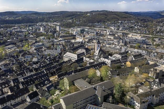 Prise de vue en grand angle d'une belle ville entourée de collines sous le ciel bleu