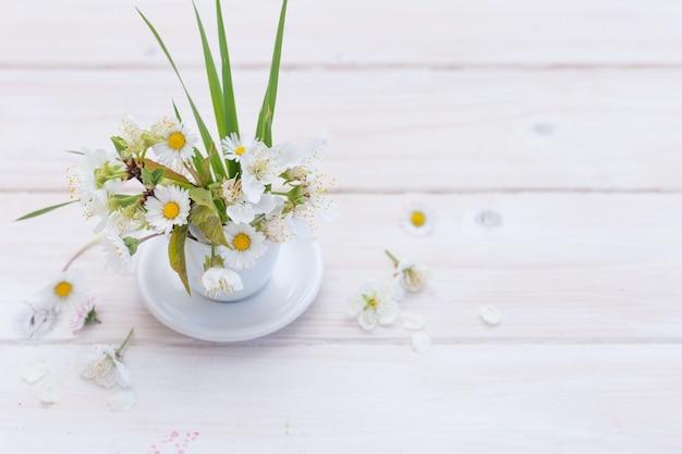 Prise de vue en grand angle de belles daises mis dans une tasse blanche