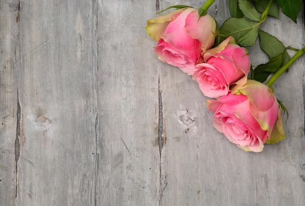 Prise de vue en grand angle des belles roses roses sur une surface en bois
