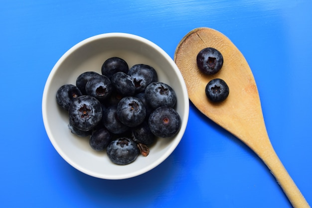 Prise de vue en grand angle d'un bol blanc avec des myrtilles près d'une cuillère en bois isolée sur un mur bleu
