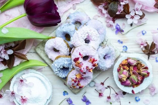 Prise de vue en grand angle de certains beignets végétaliens bleus et violets entourés de fleurs sur une table