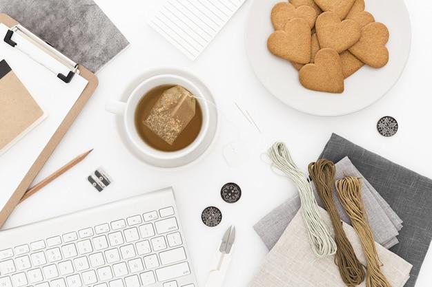 Prise de vue en grand angle d'un clavier, une tasse de thé et des biscuits, du fil et des papiers sur une surface blanche