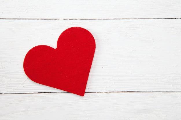 Prise de vue en grand angle d'un coeur de papier rouge isolé sur une surface en bois blanc