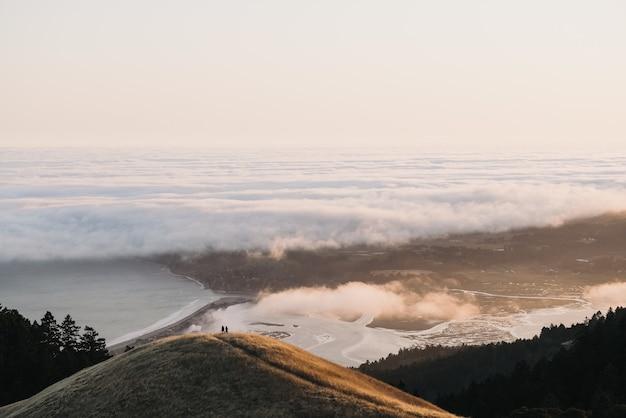 Prise de vue en grand angle de collines de différentes tailles entourant l'océan calme