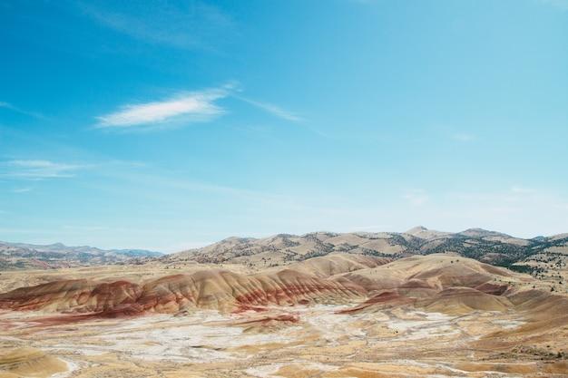 Prise de vue en grand angle des collines de sable dans une zone déserte sous le ciel lumineux