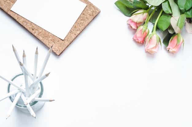 Prise de vue en grand angle de crayons blancs, papier et roses roses sur une surface blanche