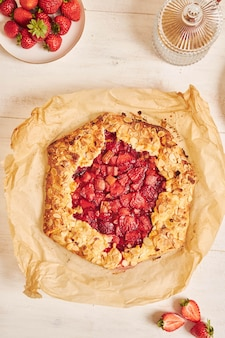 Prise de vue en grand angle de délicieux gâteau gallate de fraises à la rhubarbe avec des ingrédients sur un tableau blanc