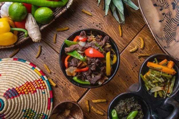 Prise de vue en grand angle de délicieux plats éthiopiens traditionnels avec des légumes sur une surface en bois