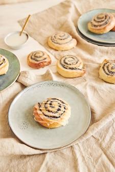 Prise de vue en grand angle de délicieux rouleaux de graines de pavot avec un glaçage au sucre sur une table