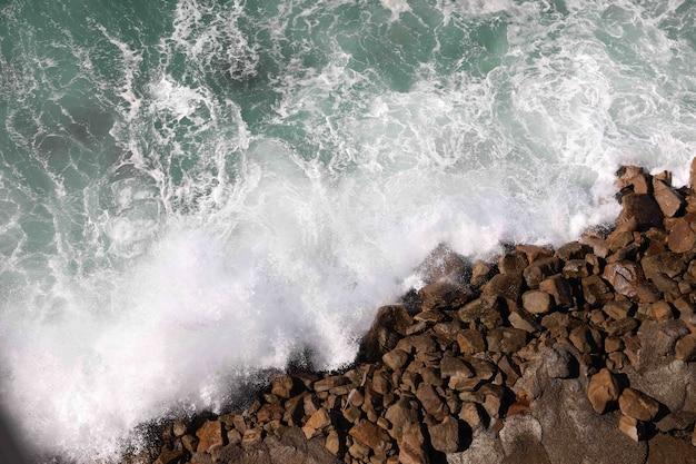 Prise de vue en grand angle d'eau éclaboussant sur les rochers de la plage
