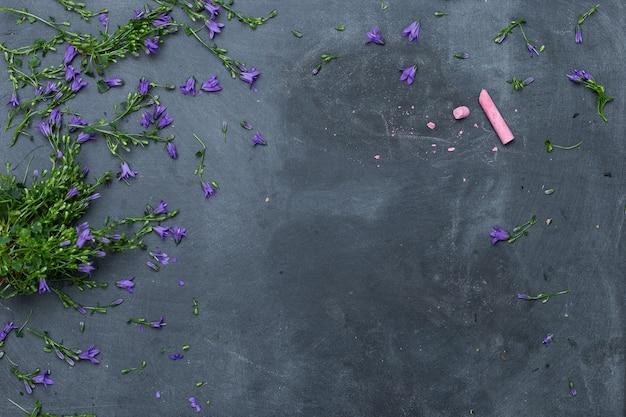 Prise de vue en grand angle de fleurs violettes réparties sur une surface noire avec une craie rose