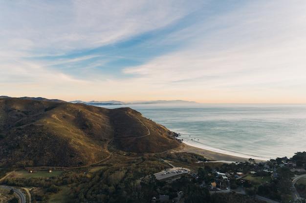 Prise De Vue En Grand Angle De L'océan à Une Formation Rocheuse Couverte De Verdure Photo gratuit