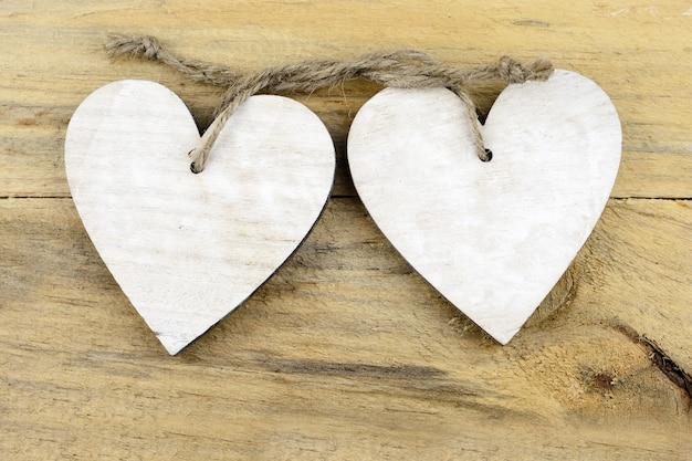 Prise de vue en grand angle d'ornements en forme de coeur en bois sur une surface en bois