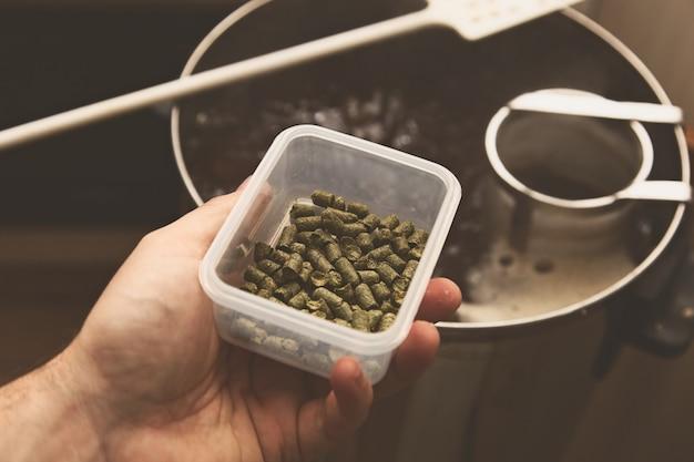 Prise de vue en grand angle d'une personne tenant un bol de quelques herbes sur un pot sur la cuisinière