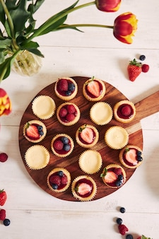 Prise de vue en grand angle de petits gâteaux au fromage avec de la gelée de fruits et des fruits sur une plaque en bois