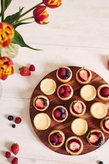 Prise de vue en grand angle de petits gâteaux au fromage avec gelée de fruits et fruits sur une plaque en bois