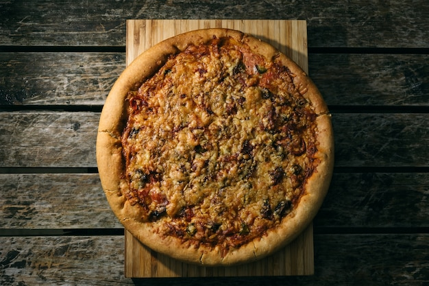Prise de vue en grand angle d'une pizza fraîchement cuite sur une surface en bois