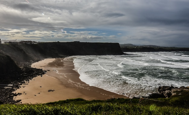 Prise de vue en grand angle d'une plage rocheuse entourée de falaises sous un ciel nuageux