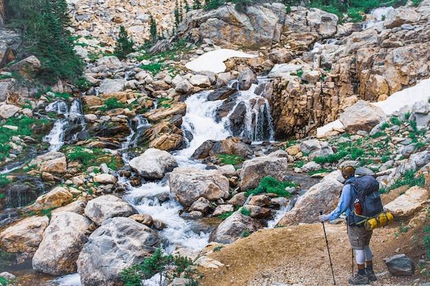 Prise de vue en grand angle d'un randonneur admirant le petit ruisseau sur les pierres