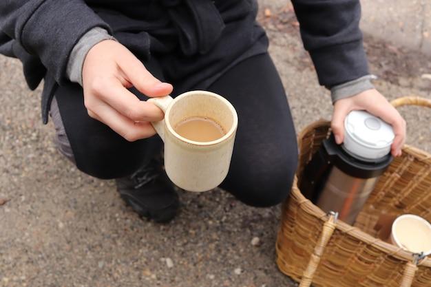 Prise de vue en grand angle d'un randonneur tenant une tasse de café et une fiole