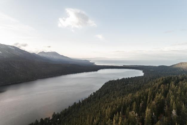 Prise de vue en grand angle d'une rivière au milieu d'un paysage verdoyant sous le ciel clair