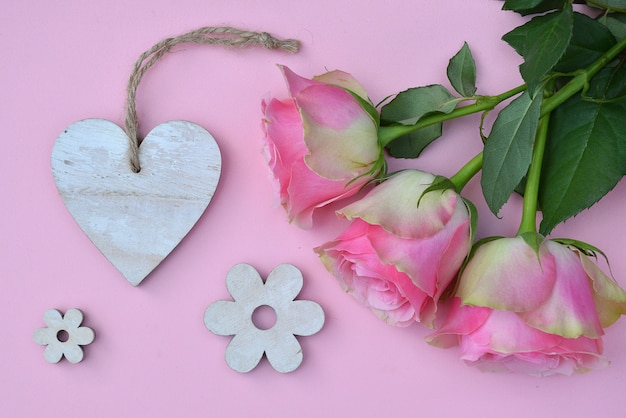 Prise de vue en grand angle de roses roses avec d'autres décorations sur une surface rose