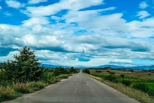 Prise de vue en grand angle d'une route dans la vallée sous le ciel avec de gros nuages blancs