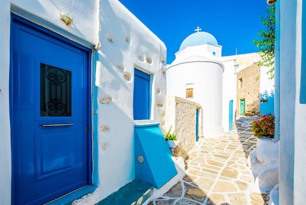 Prise de vue grand angle de la rue grecque traditionnelle avec des maisons blanches et des portes et fenêtres bleues dans les rues de lefkes, île de paros, grèce