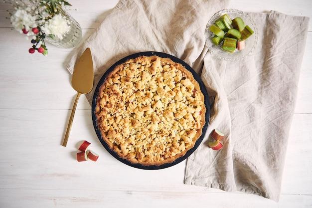 Prise de vue en grand angle d'une tarte croustillante gâteau rhabarbar et quelques ingrédients sur un tableau blanc