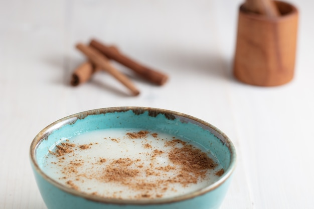 Prise de vue en grand angle d'une tasse de lait avec de la cannelle et des bâtons de cannelle sur une surface blanche
